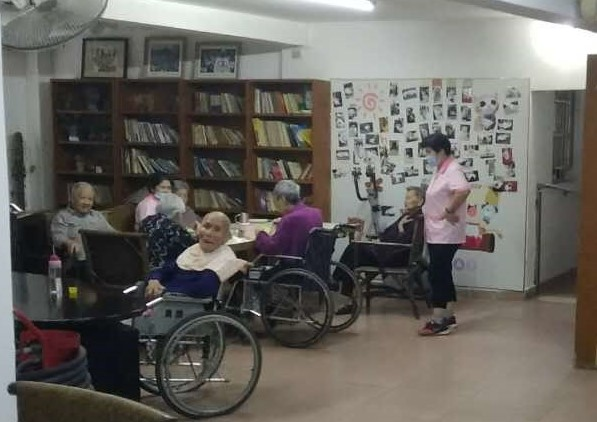 Many old people are having dinne with few care workers in Haochen Nursing Room